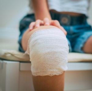Child knee with adhesive and gauze bandage.