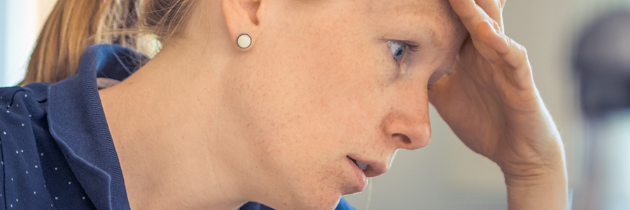 Woman stressed with head pain. Loss of senses is one of the hardest symptoms of brain injury.