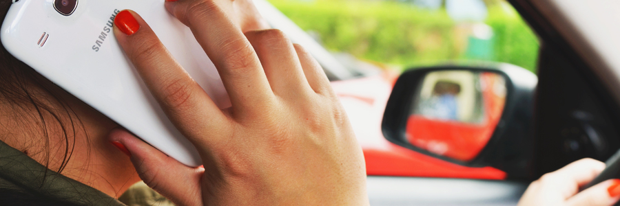 Girl talking on phone while driving. Contact Conte and associates if you've been the victim of a texting and driving accident.