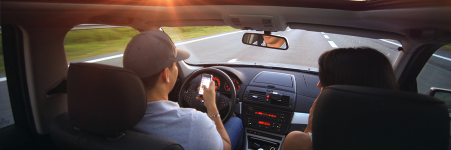 Couple driving in a car, with driver texting behind the wheel. Texting and driving laws and fines in Ontario. Contact Conte and Associates, personal injury lawyers, located in Whitby and Vaughan.