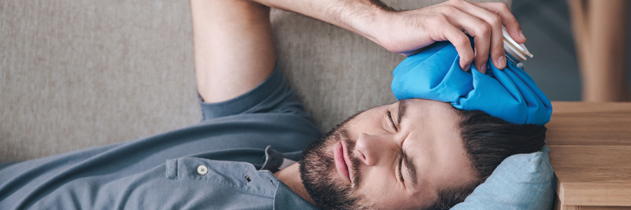 Man suffering from head injury, lying on couch with an ice pack on his head.