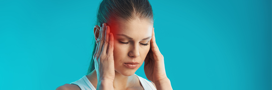 Woman suffering a headache. This is one of the signs of an anoxic brain injury.