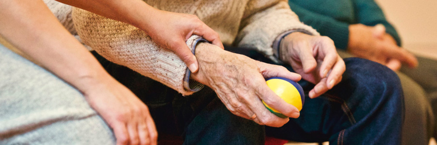 Caregiver hand on elderly arm. Cognitive brain injury symptoms are important to know.