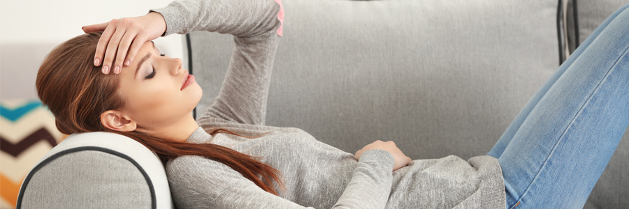 Woman laying on couch with head pain. Signs of brain injury can include headache and physical symptoms.