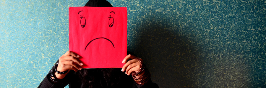 Depressed person holding sad face. Dealing with the signs and symptoms of brain injury is hard.