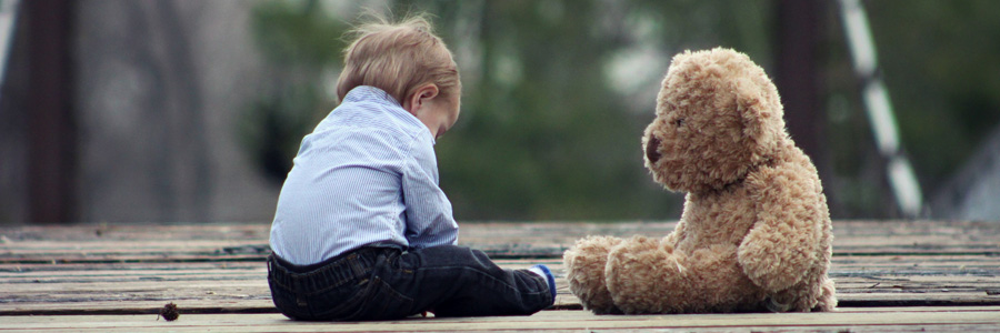 Child sitting alone with teddy bear. Head injury in children can cause serious brain issues.