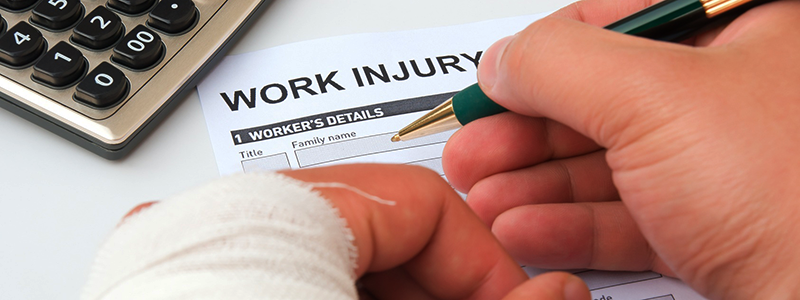 Man filling out WSIB workplace injury insurance claim form