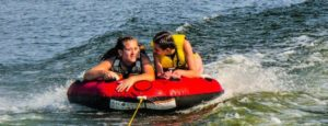 two girls in a tube in the water in summertime. Peak time for brain injuries. Conte Jaswal Personal Injury Lawyers in Oshawa, Whitby, and Vaughan.